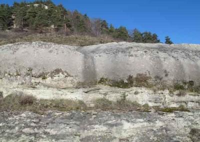 Les barres de grès, horizontales, reposent sur les schistes altérés, couleur lie-de-vin.